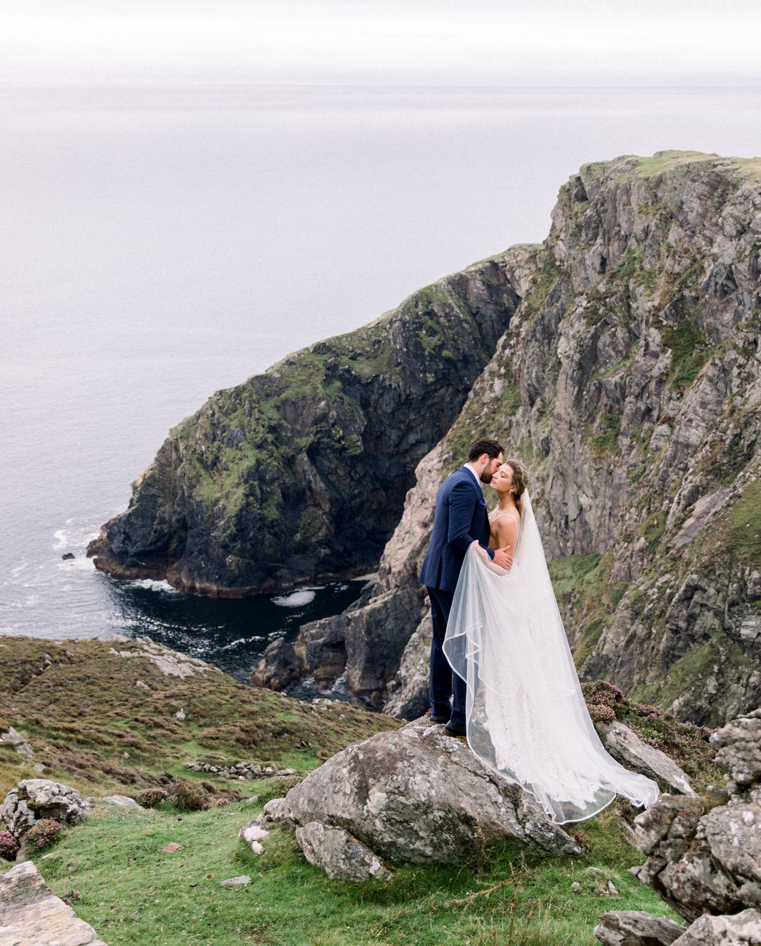 Bride and groom overlooking a majestic Ireland bluff.