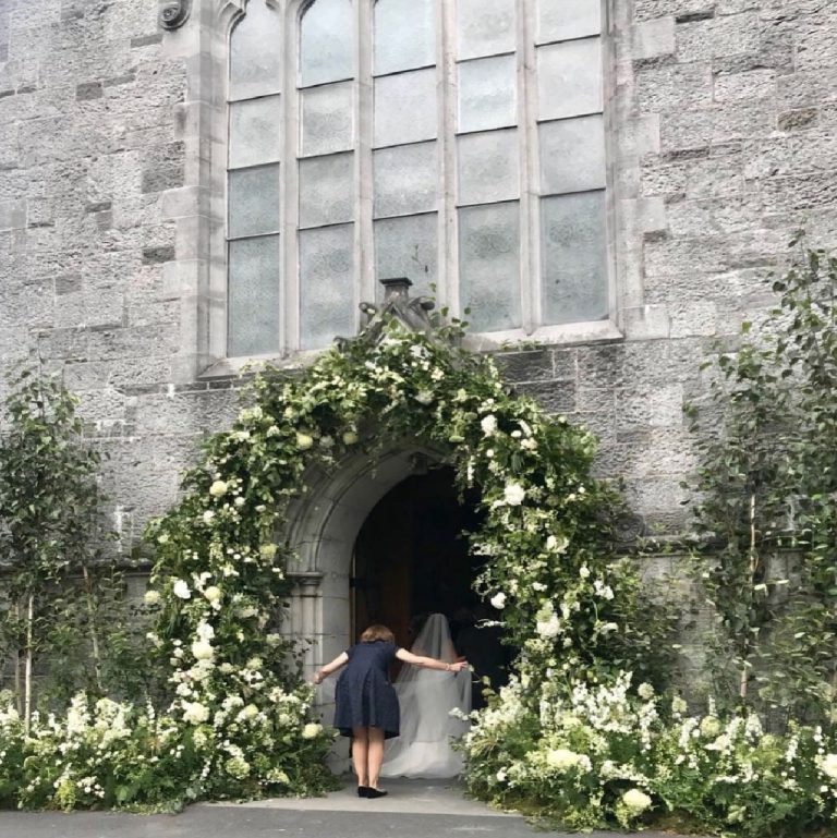 Bride entering church as planner holds wedding dress.