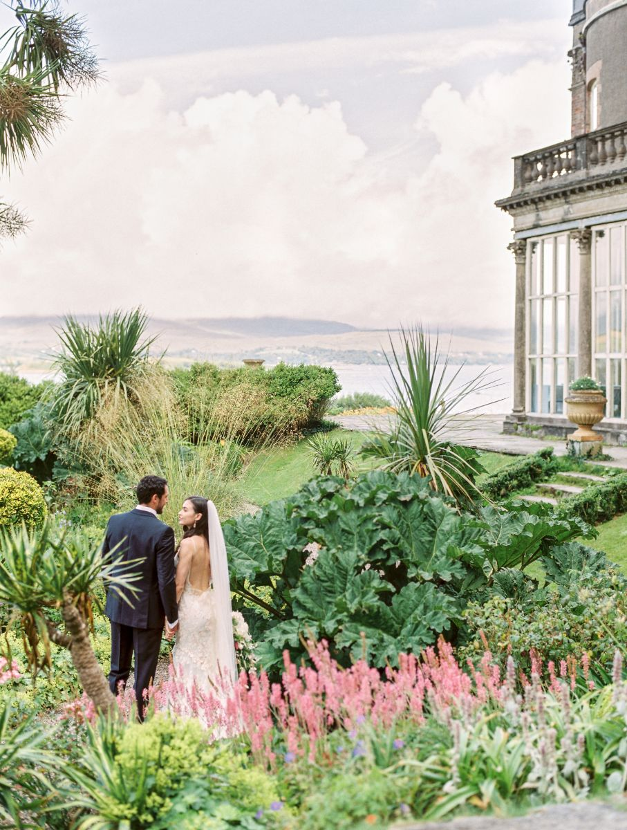 Bride and groom looking over tropical garden following destination wedding.