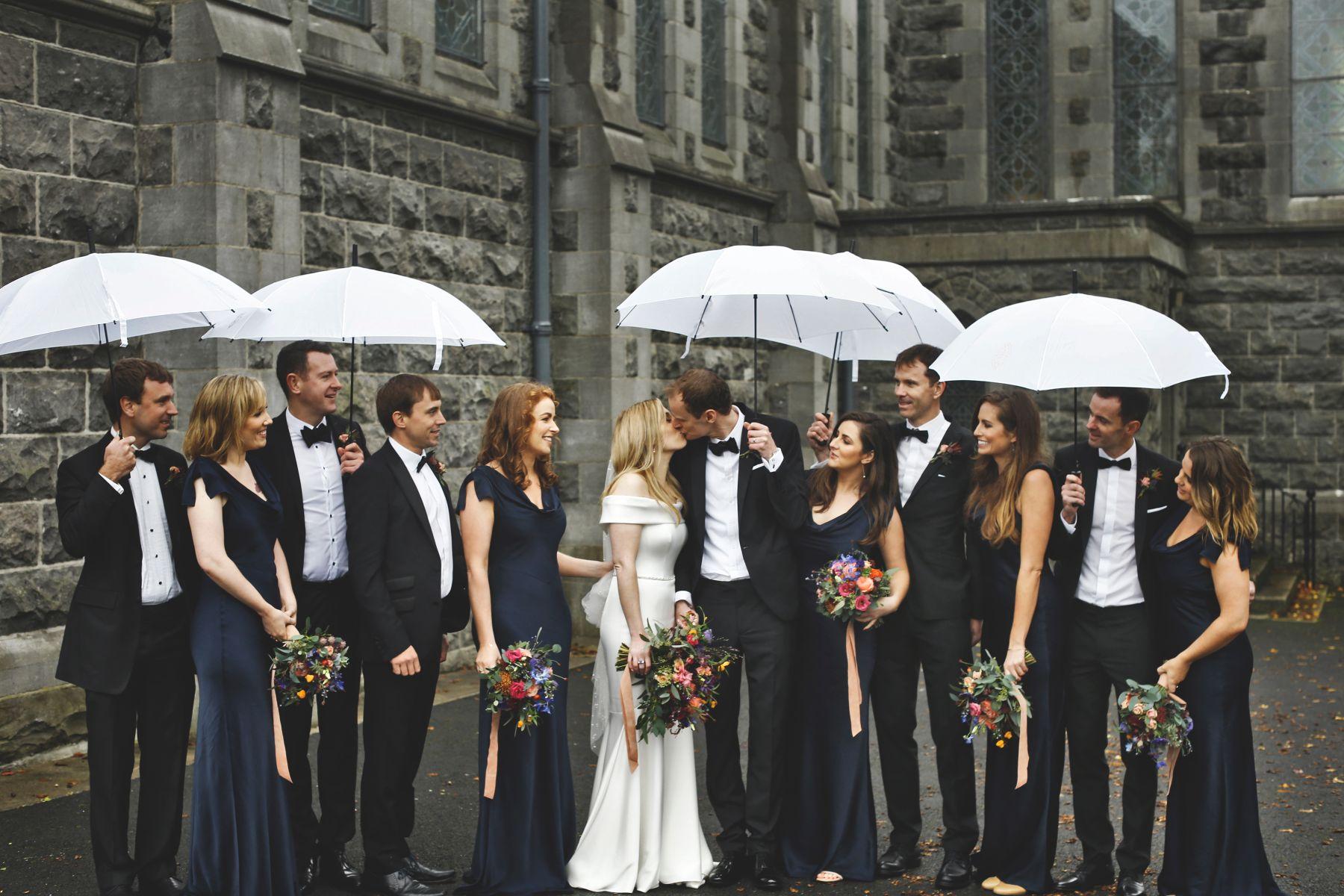 Wedding party with umbrellas.