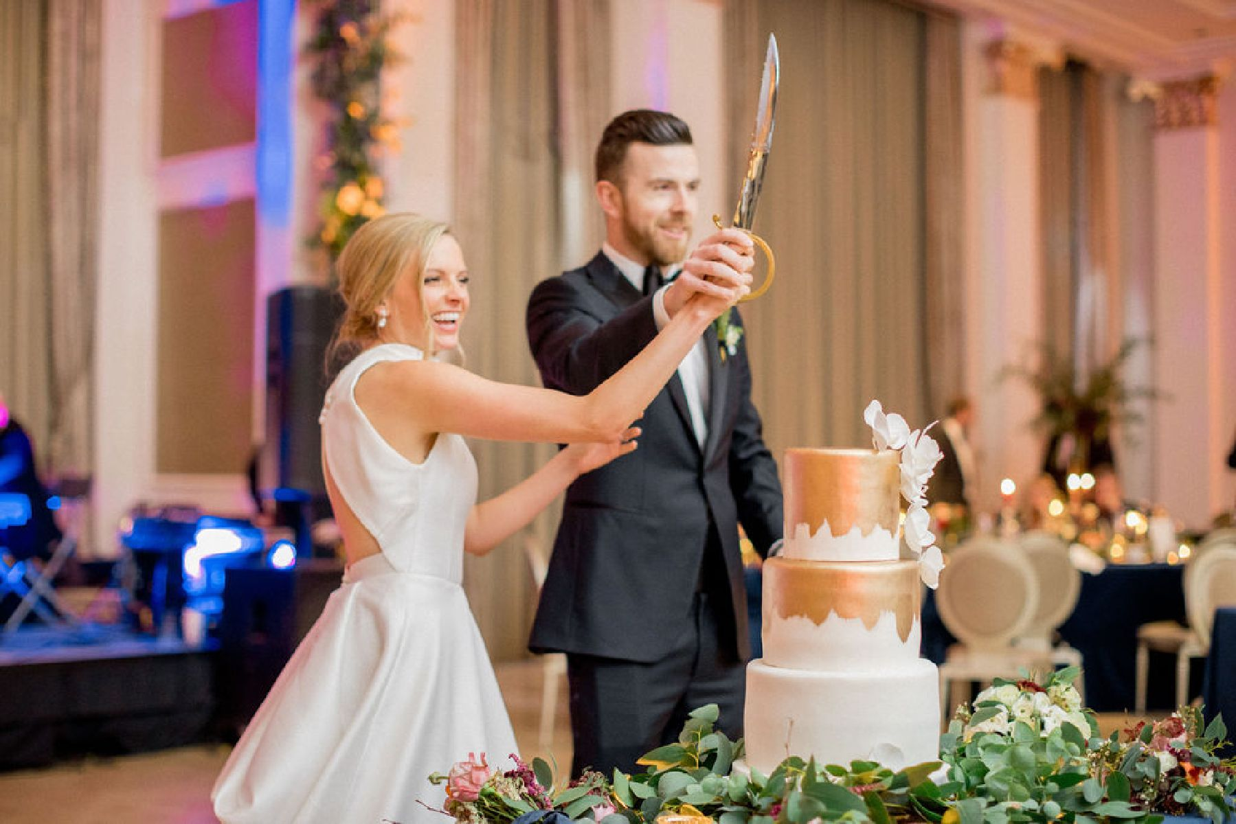 Bride and groom cutting cake with sword.