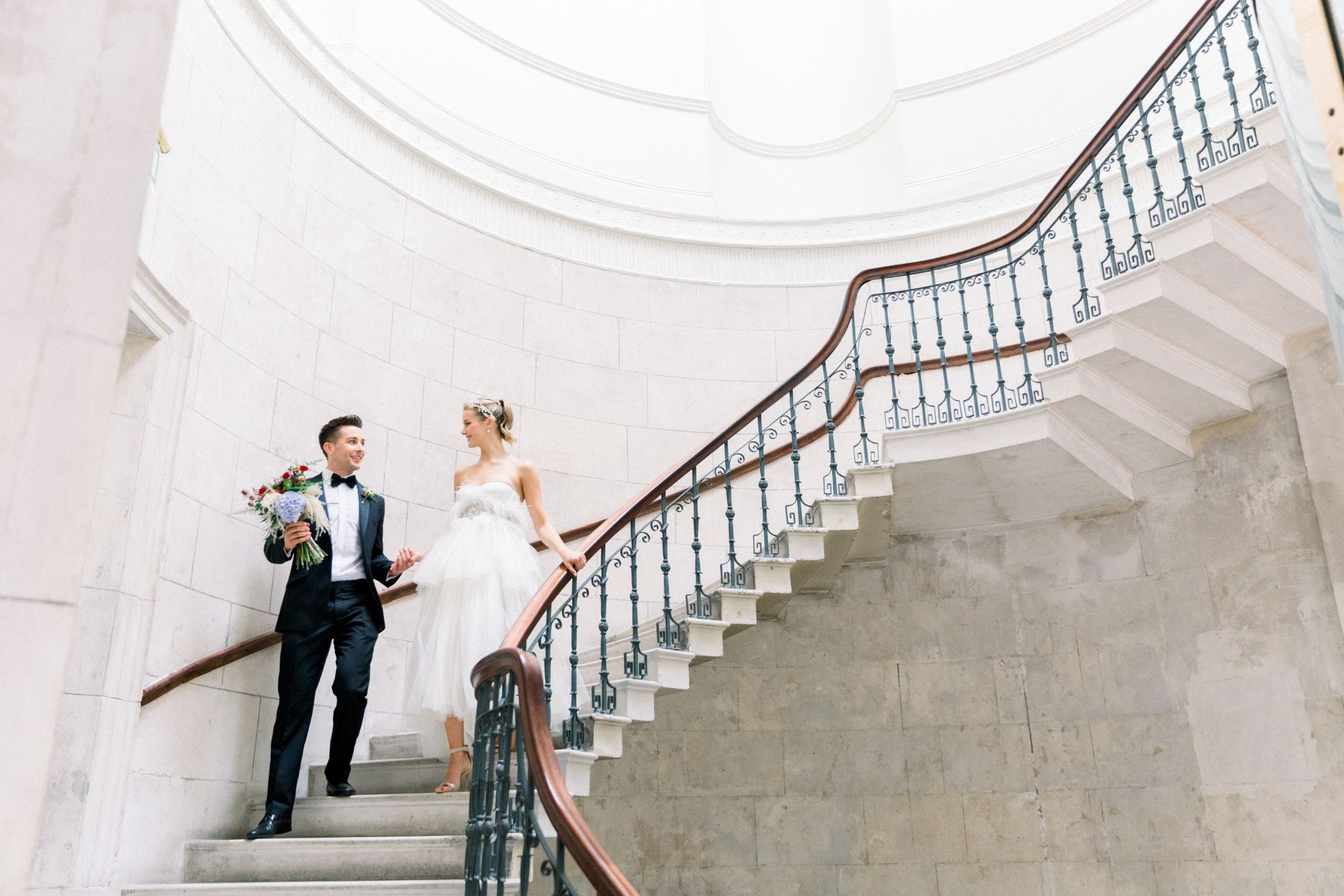 Bride and groom posing on stairwell in city hall.