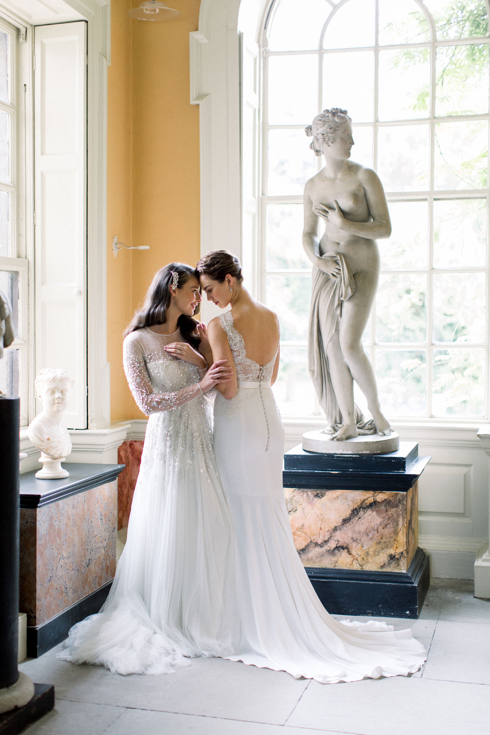 Two brides embracing.