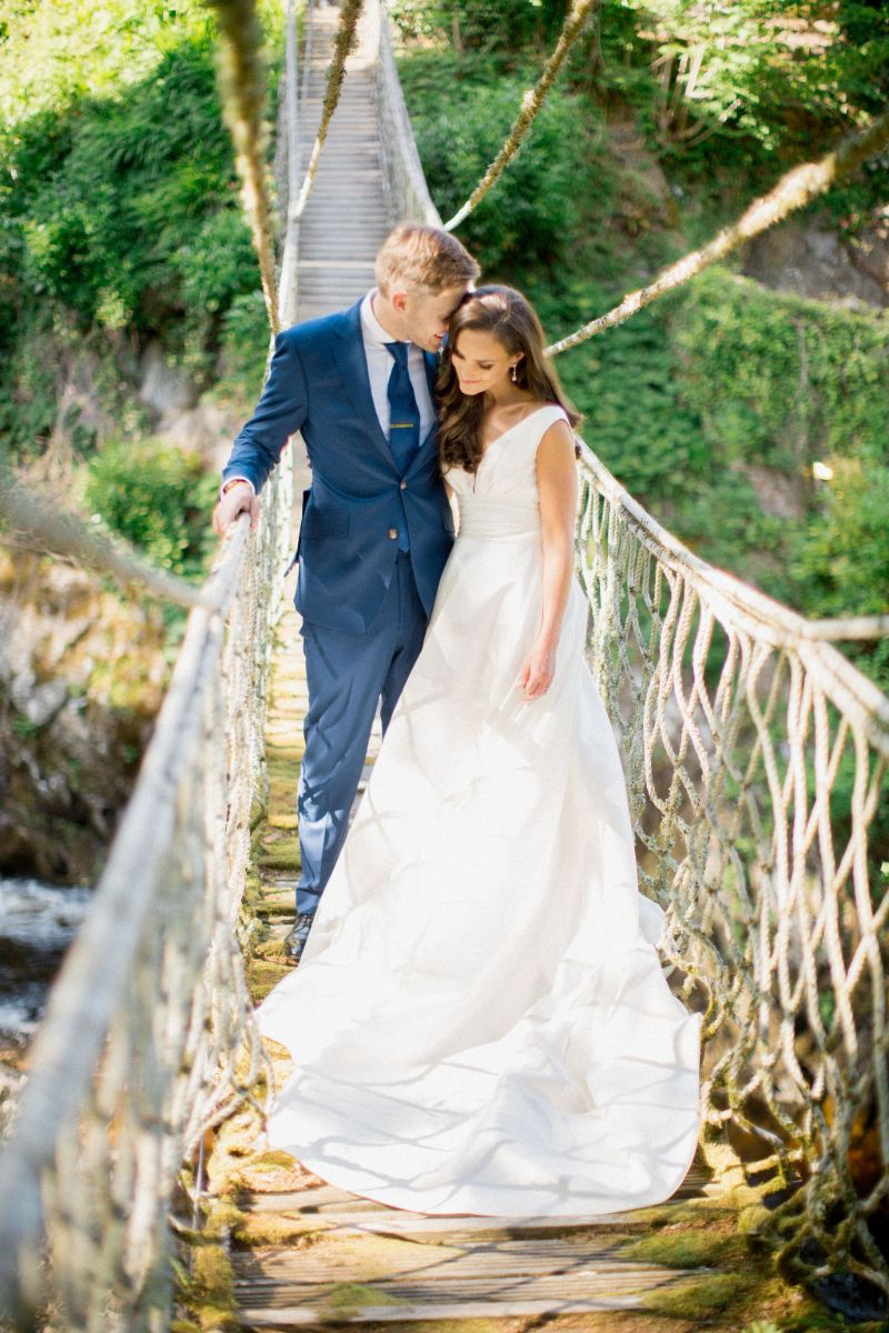 Bride and groom standing on a rope bridge.