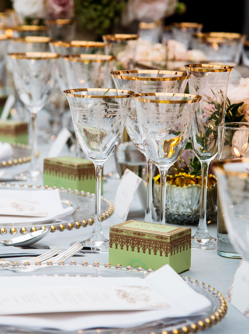 A party table setting with gold rimmed glasses.
