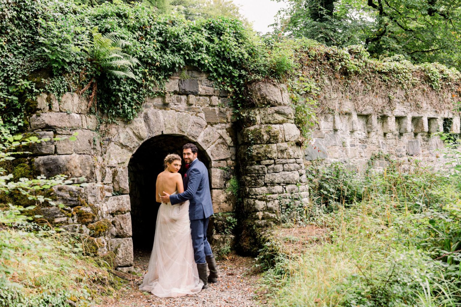 Bride and groom standing in front of a tunnel in Ireland.