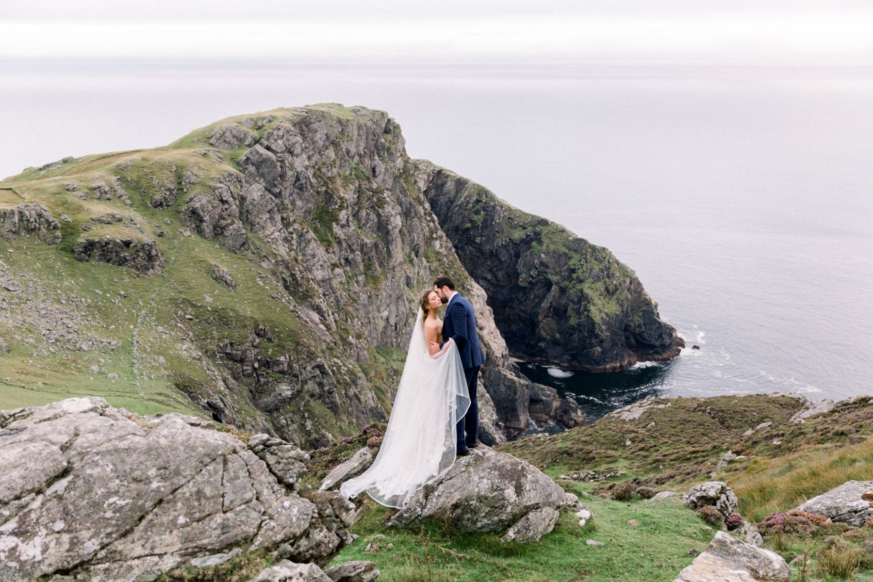 Bride and Groom embracing overlooking the sea.