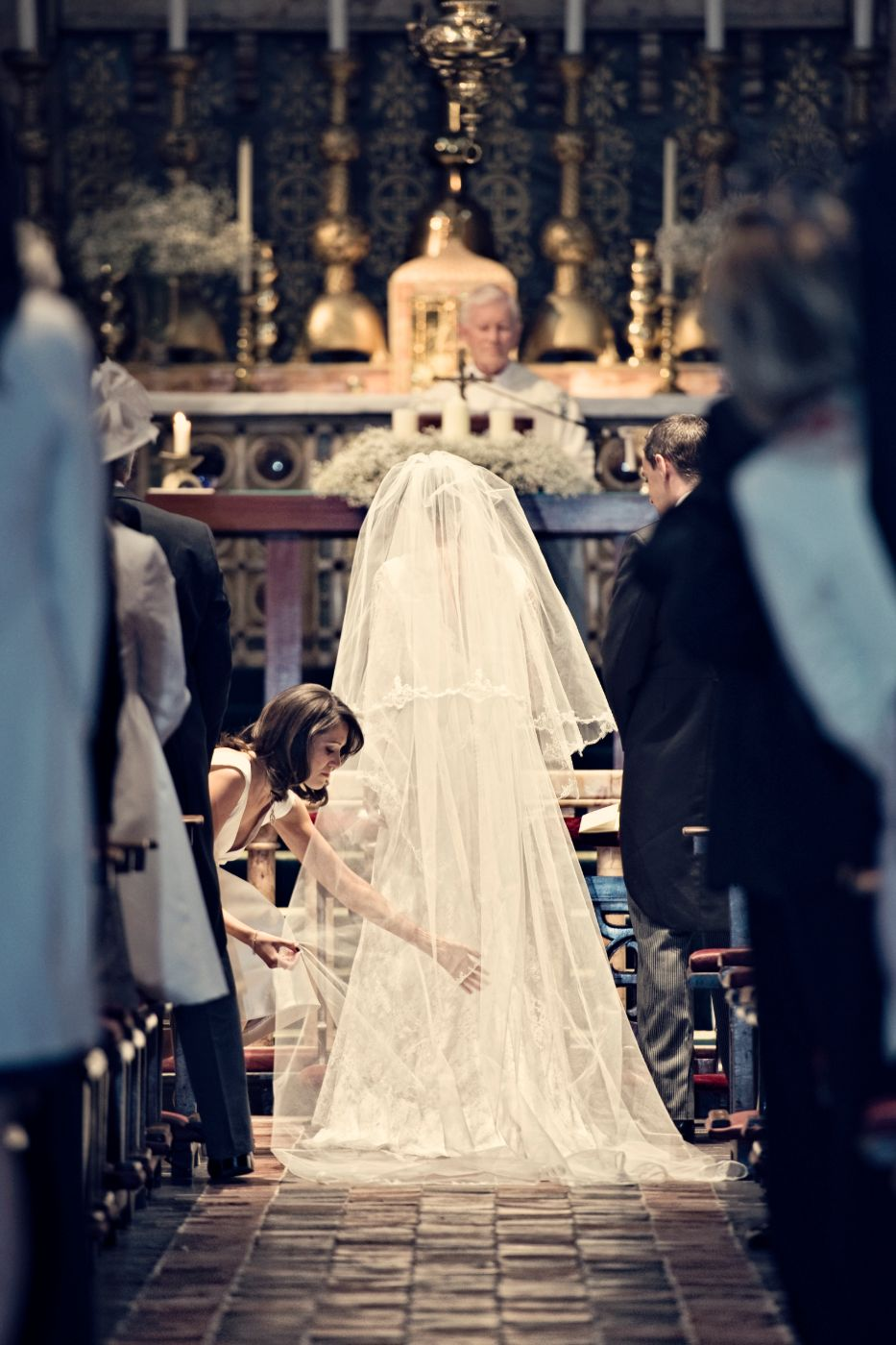 Tara adjusting bride's trailing dress.