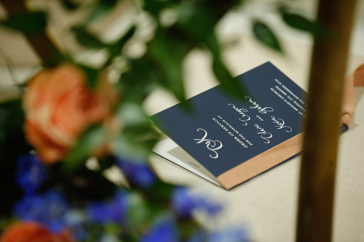 navy blue wedding program with peach velvet ribbon