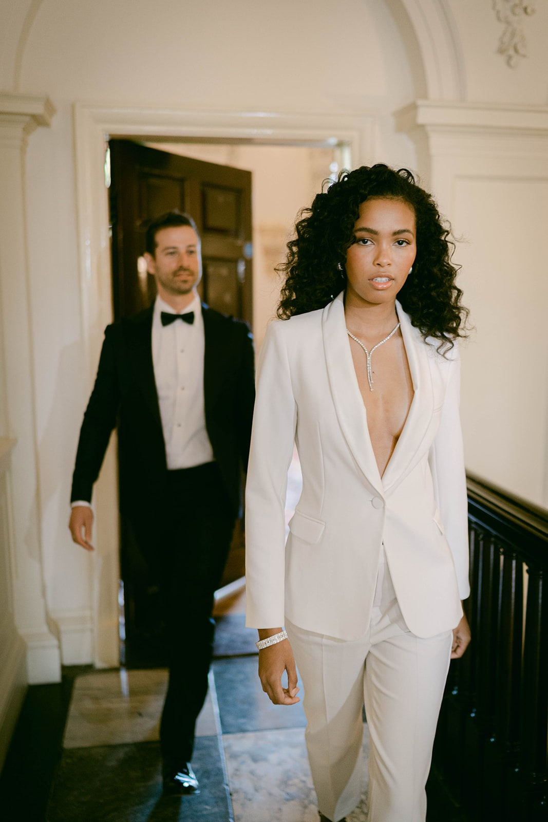 bride in white pantsuit and diamond necklace